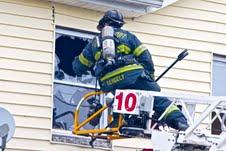 FF Dennis Gergely of Ladder 10 working to vent 2nd floor.